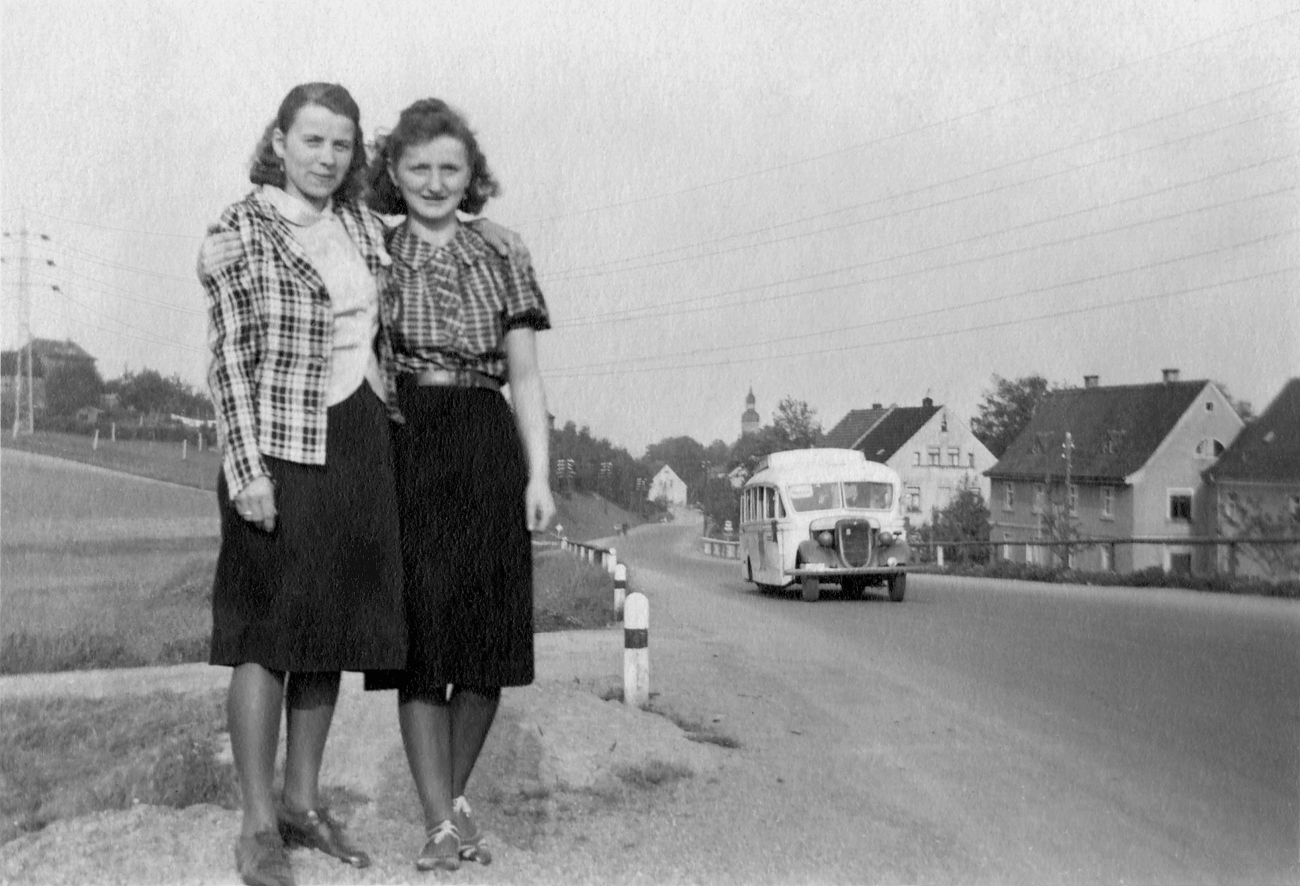 Zwei vor Ueberlandleitung an Dorfstrasse mit Bus